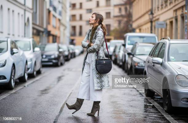 Masha Sedgwick is seen wearing coat with snake print Topshop olive wild leather boots Santoni white croped pants Joseph olive zip sweater Gestuz...
