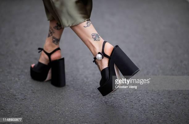 Masha Sedgwick is seen wearing green silk Topshop midi skirt, Miu Miu high plateau sandals on May 11, 2019 in Berlin, Germany.