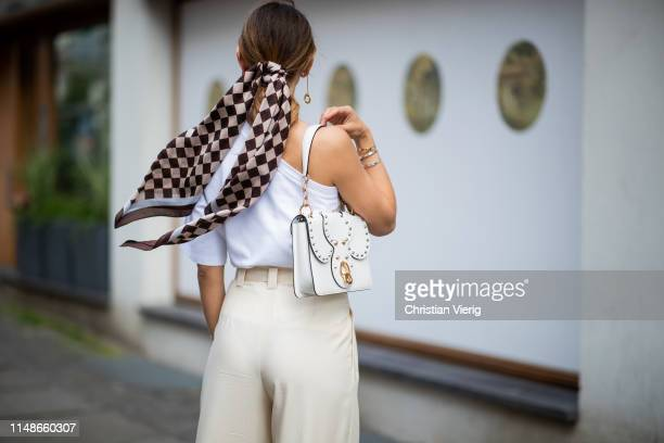 Masha Sedgwick is seen wearing plaid scarf Baum und Pferdgarten, white ripped off Max Mara tshirt, beige wide leg pants Mango, white Miu Miu bag on...