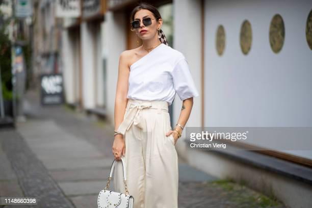Masha Sedgwick is seen wearing plaid scarf Baum und Pferdgarten white ripped off Max Mara tshirt beige wide leg pants Mango white Miu Miu bag...