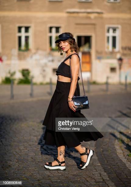 Masha Sedgwick wearing a black cropped top Ulla Johnson black midi skirt Strenesse Zara plattform sandals Fendi bag Calvin Klein cap YSL bangle on...