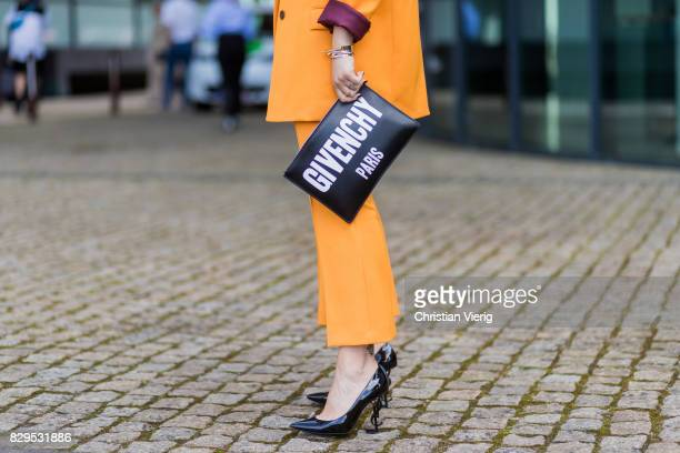 Masha Sedgwick wearing a yellow Lala Berlin suit Givenchy clutch and tshirt YSL shoes outside Designers Remix on August 10 2017 in Copenhagen Denmark