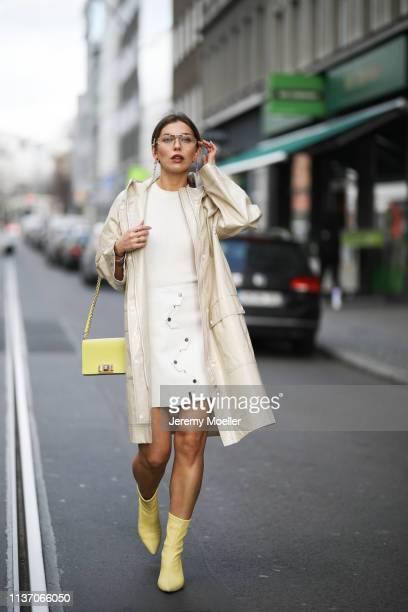 Masha Sedgwick wearing Arket white knit shirt, Pinko white leather skirt, yellow Furla bag, yellow Anine Bing, Celine glasses, Tiffany & Co earring,...