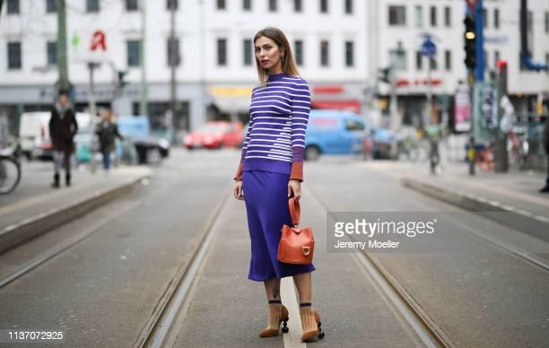Masha Sedgwick wearing Asos royal blue skirt System violet striped shirt Danse Lente orange bucket bag Jacquemus brown wild leather pumps Happy socks...