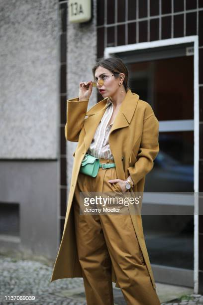Masha Sedgwick wearing Bally wide pants Sandro stripes shirt Bash mustard yellow coat green Aigner belt bag Marc Jacobs sunnies Tiffany Co earring on...
