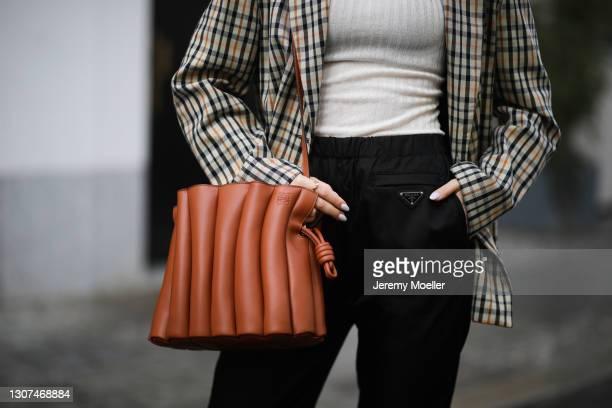 Masha Sedgwick wearing black Prada nylon pants, vintage blazer, beige Baum & Pferdgarten top and brown Loewe leather bag on March 15, 2021 in Berlin,...