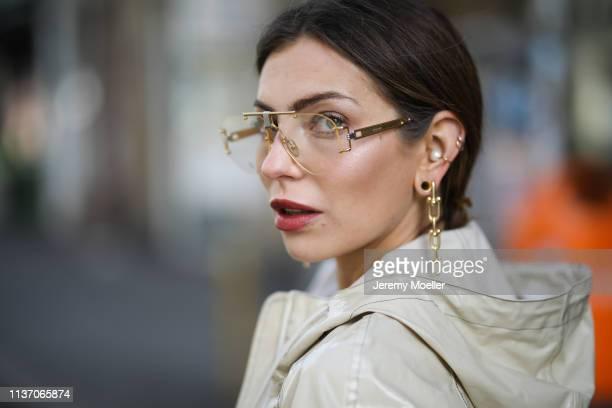 Masha Sedgwick wearing Celine glasses, Tiffany & Co earring, 8 by yoox beige vinyl coat on March 19, 2019 in Berlin, Germany.