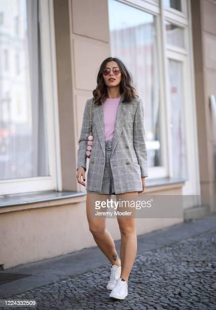 Masha Sedgwick wearing Coach sneaker, Ray Ban shades, Envii shirt and Sandro shorts, jacket and bag on May 06, 2020 in Berlin, Germany.