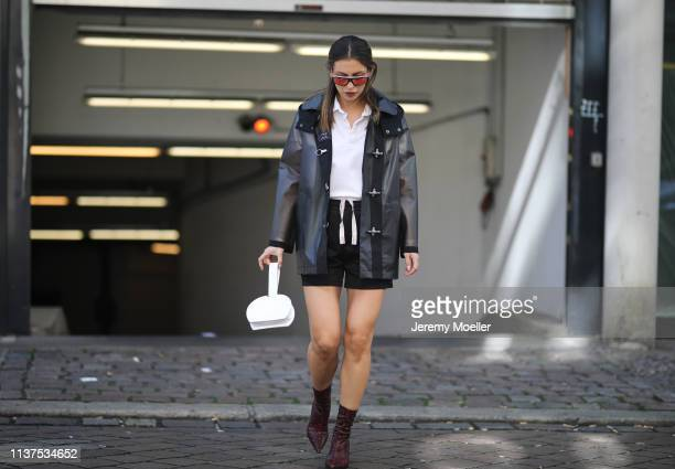 Masha Sedgwick wearing Fay Rain Coat, white Lacoste polo shirt, Acne sporty track shorts, Mango Stiletto Sock boots with snake print in red & black,...