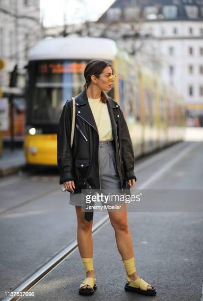 Masha Sedgwick wearing Gestuz citrus light yellow shirt, Acne Studio oversized leather jacket, AGL yellow plateau sandals, grey Frankie shop shorts,...