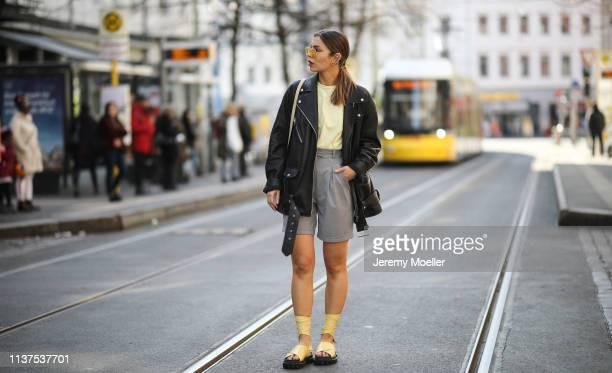 Masha Sedgwick wearing Gestuz citrus light yellow shirt Acne Studio oversized leather jacket AGL yellow plateau sandals grey Frankie shop shorts...