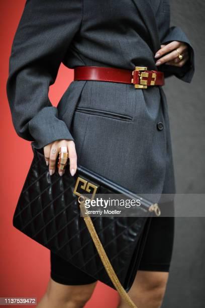 Masha Sedgwick wearing grey ami oversized blazer, Givenchy clutch, Vintage belt, Tiffany earrings on March 20, 2019 in Berlin, Germany.