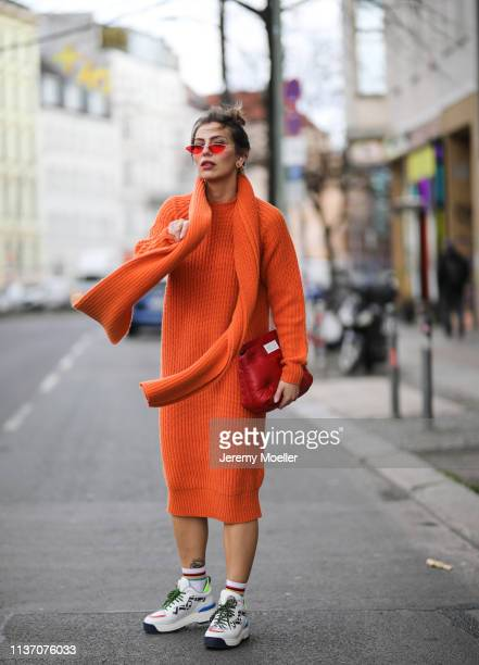 Masha Sedgwick wearing orange sweater dress via Asos Fendi Ugly Dad sneakers Asos red mini sunglasses Rainbow socks on March 19 2019 in Berlin Germany
