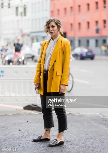 Masha Sedgwick wearing yellow blazer jacket black cropped two tone pants slippers white bag during the MercedesBenz Fashion Week Berlin Spring/Summer...