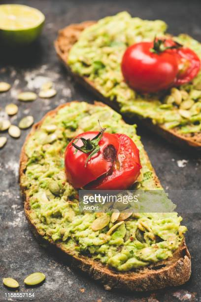 mashed avocado and roasted tomato on bread - toasted bread stock pictures, royalty-free photos & images
