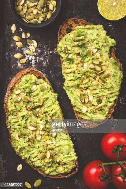mashed avocado on toasted bread - avocado toast stockfoto's en -beelden