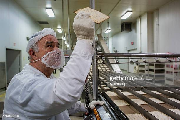 A Mashgiach a Jew who supervises the kashrut status of a kosher establishment inspects Passover matzo after it comes out of an oven at the...