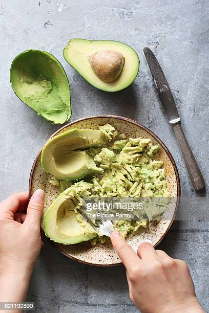 Mashing avocado for guacamole in a  bowl.Top view
