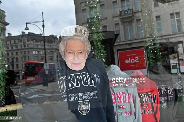 Mask depicting Britain's Queen Elizabeth II is pictured on a display of clothing in the window of a souvenir shop, closed sue to Covid-19, on Oxford...