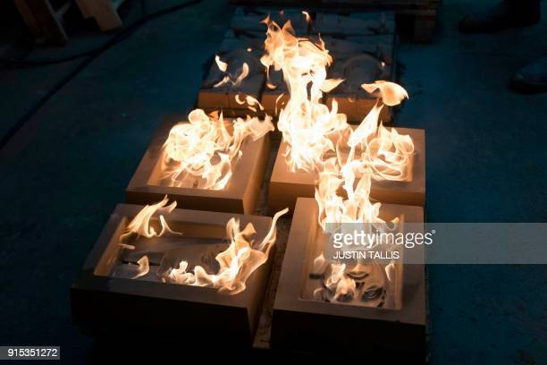 mask moulds are set alight to burn off any impurities before casting during a photo call at the New Pro Foundries west of London on February 7 2018...