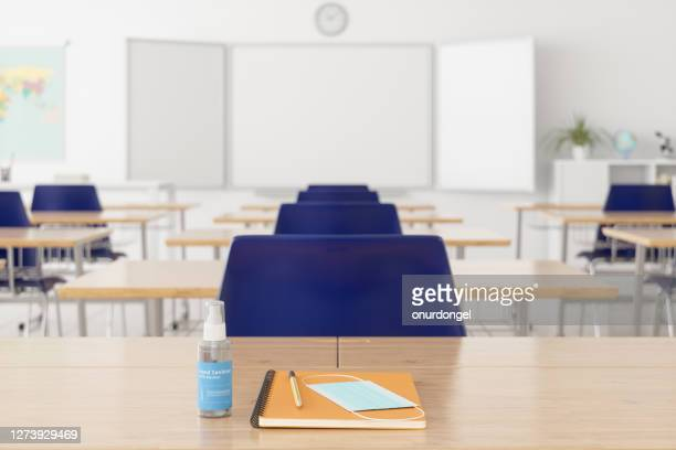 mask, notebook and pencil on the desk with blurred empty classroom - reopening stock pictures, royalty-free photos & images