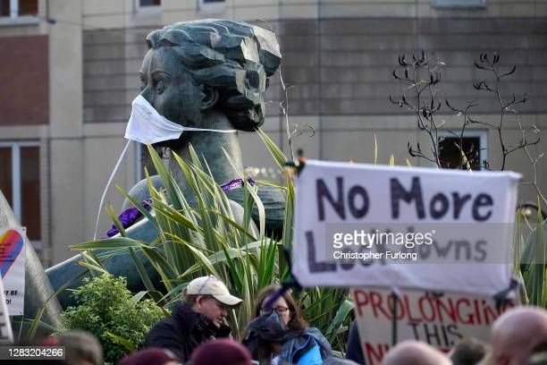 A mask sits on a sculpture named The River during a demonstration against a second lockdown in Victoria Square on October 31 2020 in Birmingham...