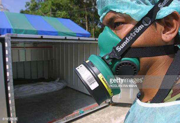 A mask Thai soldier waits to bring out bodies from a container freezer at a makeshift morgue in Krabi southern Thailand 06 January 2005 Over 146000...