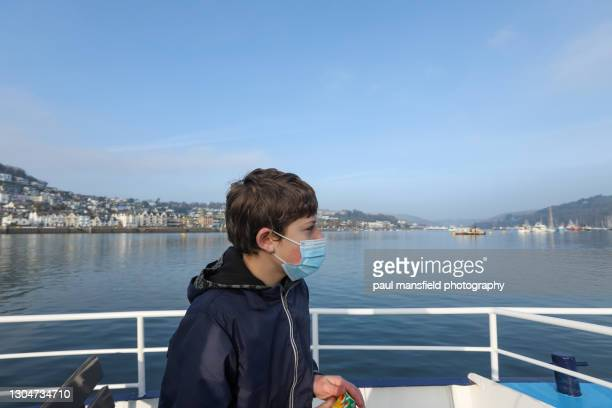 mask wearing child on dartmouth passenger ferry - passenger craft stock pictures, royalty-free photos & images