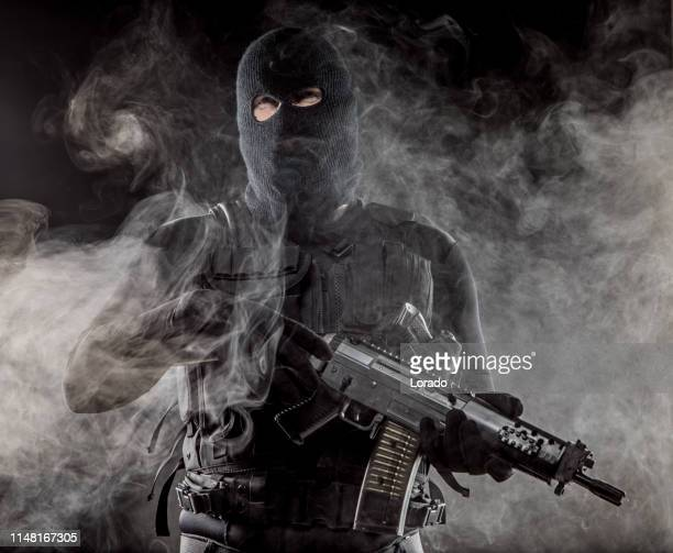 mask wearing lone soldier in smoky indoor urban setting - terrorism stock pictures, royalty-free photos & images