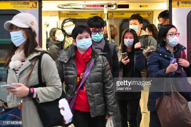 Mask-clad commuters get off a train at a Mass Rapid Transit stop in Taipei following the Lunar New Year holidays on January 30, 2020. - Taiwan has...