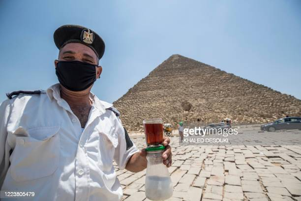 Mask-clad Egyptian policeman on duty at the Giza Pyramids necropolis walks while holding a glass of tea and a jar of sugar past the Great Pyramid of...