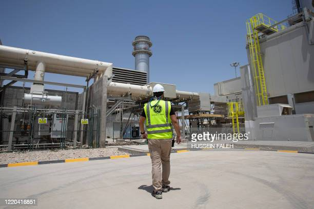 Mask-clad General Electric employee tours the Dhi Qar Combined Cycle Power Plant near the Iraqi city of Nasiriyah on June 15, 2020.