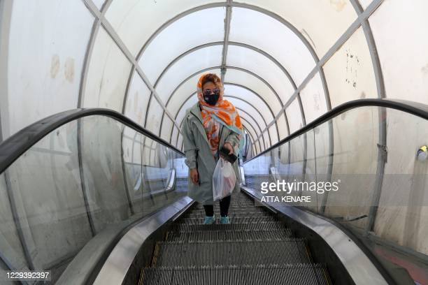 Mask-clad Iranian woman takes an escalator on her way to shop in Tajrish square in the capital Tehran on November 1 amid the novel coronavirus...