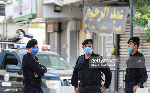 Mask-clad Jordanian policemen man a checkpoint as they enforce a COVID-19 coronavirus lockdown in the capital Amman on October 9, 2020.