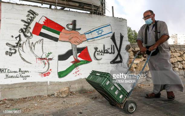 Mask-clad man pushes a cart past a graffiti depicting hands with sleeves coloured in the UAE and Bahrain flags shaking hands with another with a...