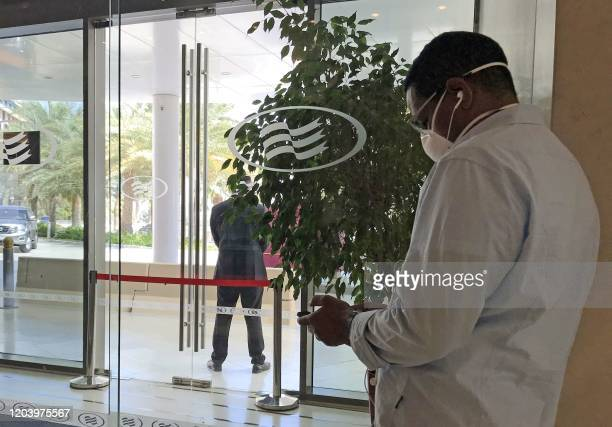 A maskclad man uses his mobile phone while standing at the entrance of the Crowne Plaza hotel in Yas Island Abu Dhabi where two Italian cyclists...