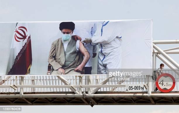 Mask-clad man walks accross a bridge along which a banner showing Iran's supreme leader Ayatollah Ali Khamenei receiving a vaccine against the...