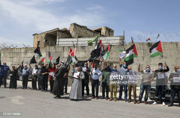 Mask-clad Palestinians demonstrate along the controversial separation barrier at the western entrance of the northern West Bank city of Tulkarem on...