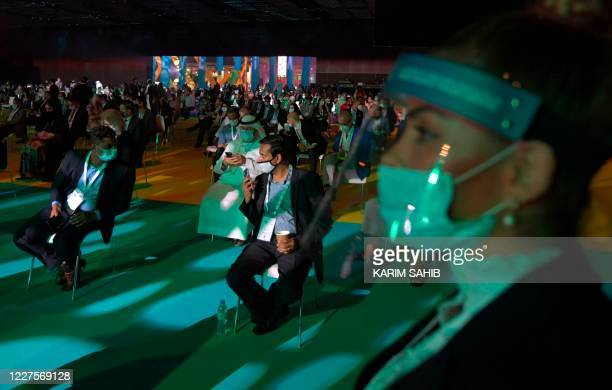 """Mask-clad participants at the first """"real life"""" conference since the coronavirus protective restrictions were put in place in March, are pictured in..."""