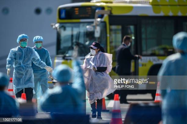 A maskclad passenger heads for a temperature check after disembarking from the Diamond Princess cruise ship in quarantine due to fears of new COVID19...