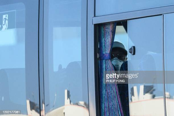 A maskclad passenger looks on from a bus after disembarking from the Diamond Princess cruise ship in quarantine due to fears of new COVID19...