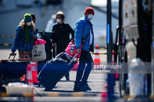Maskclad passengers prepare to board a bus after disembarking from the Diamond Princess cruise ship in quarantine due to fears of new COVID19...