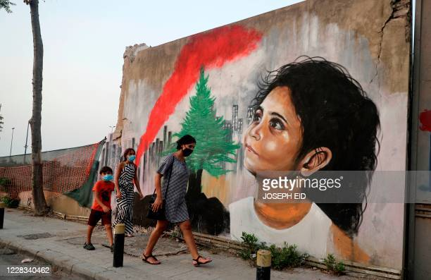 Mask-clad pedestrians walk past a mural painting on September 4 depicting a young Lebanese girl who suffered a face injury in the August 4 massive...