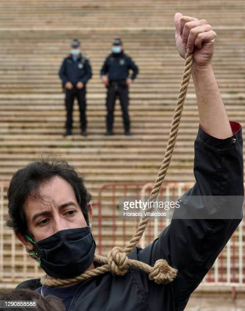 Mask-clad police officers look at a member of Climaximo movement wearing a protective mask while pulling a noose during a protest for the failure of...