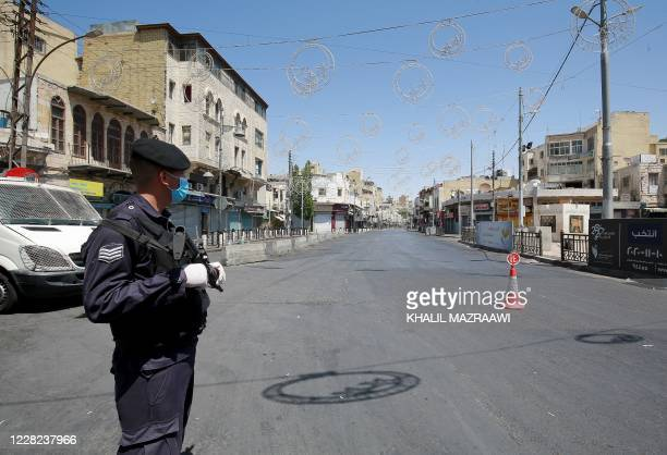 Mask-clad policeman stands on guard while enforcing a curfew due to the COVID-19 coronavirus pandemic along a street in Jordan's capital Amman on...