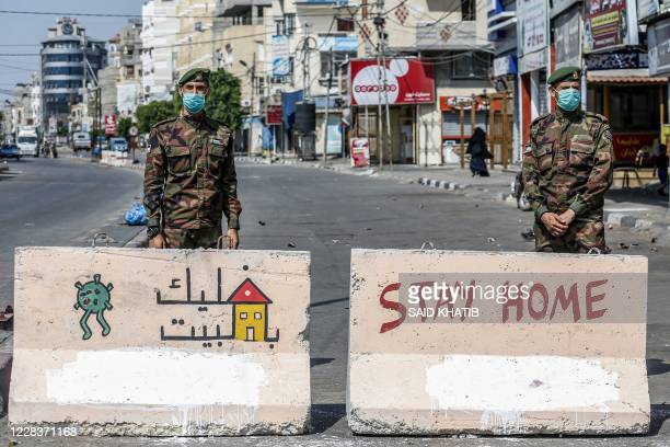 Mask-clad policemen loyal to Hamas stand behind concrete barriers painted with messages instructing people to remain at home due to the COVID-19...