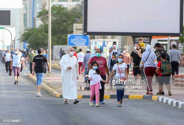 Mask-clad residents walk in a neighbourhood of Kuwait City on May 12 as authorities allowed people to exercise for two hours under a nationwide...