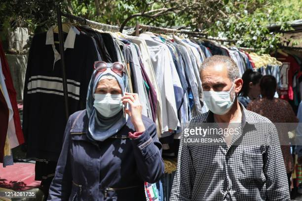 Mask-clad Syrians shop for clothes at a flea market in the capital Damascus on May 17 amid severe economic crisis that has been compounded by a...