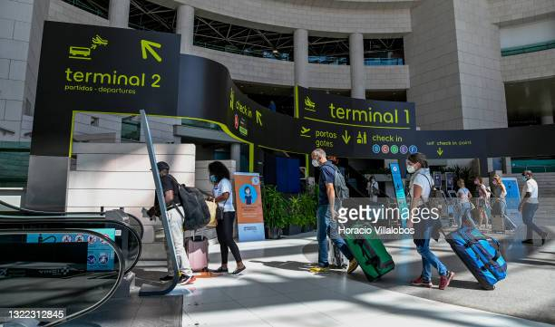 Mask-clad travelers push a luggage cart in Humberto Delgado International Airport a day before the country is taken off the UK's green list, imposing...