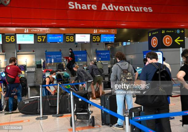 Mask-clad travelers queue at British Airways desks in Terminal 1 of Humberto Delgado International Airport a day before the country is taken off the...